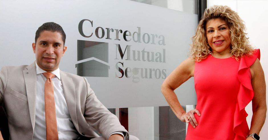 Hombre sentado y mujer de pie de rojo frente logo de Mutual Seguros