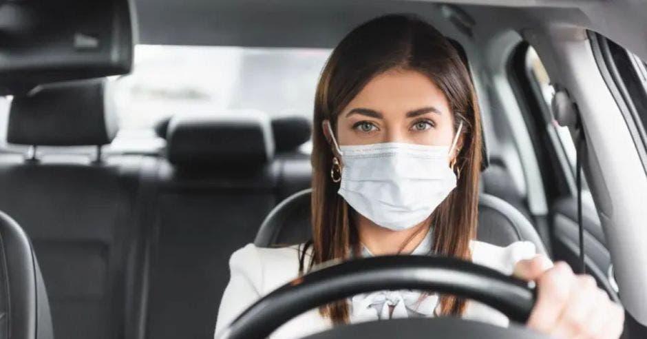 mujer con mascarilla conduciendo automóvil