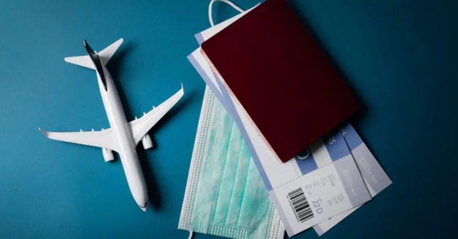 avion pequeño a la par de una pasaporte, boletos y mascarilla