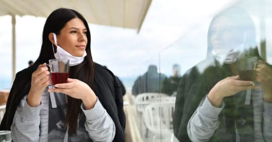 mujer con la mascarilla en la barbilla, tomando té en un balcón