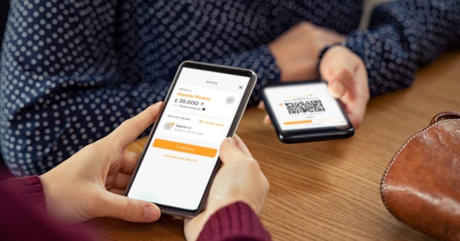 emprendedor y usuario haciendo pago por código QR en celular