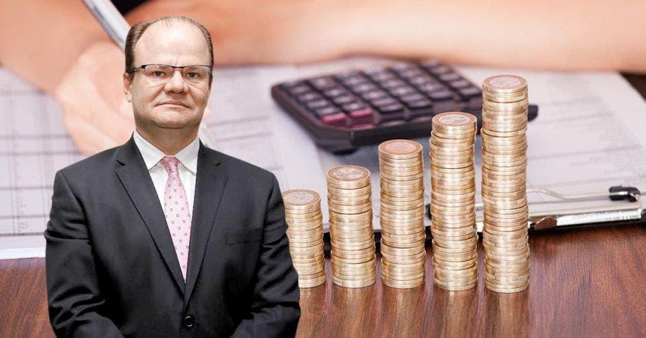 Hombre de traje frente a arte de monedas en columna