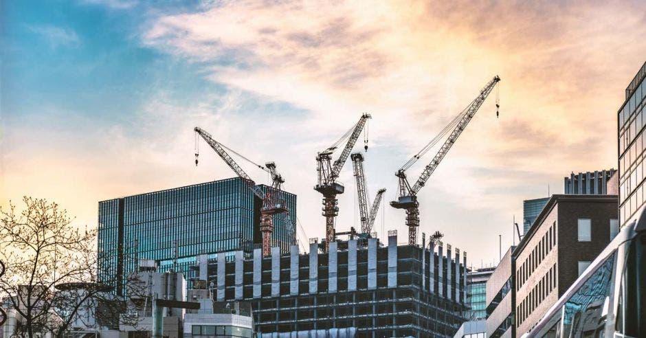 Cuatro grúas operando en la construcción de una torre de oficinas, con una tarde soleada de fondo