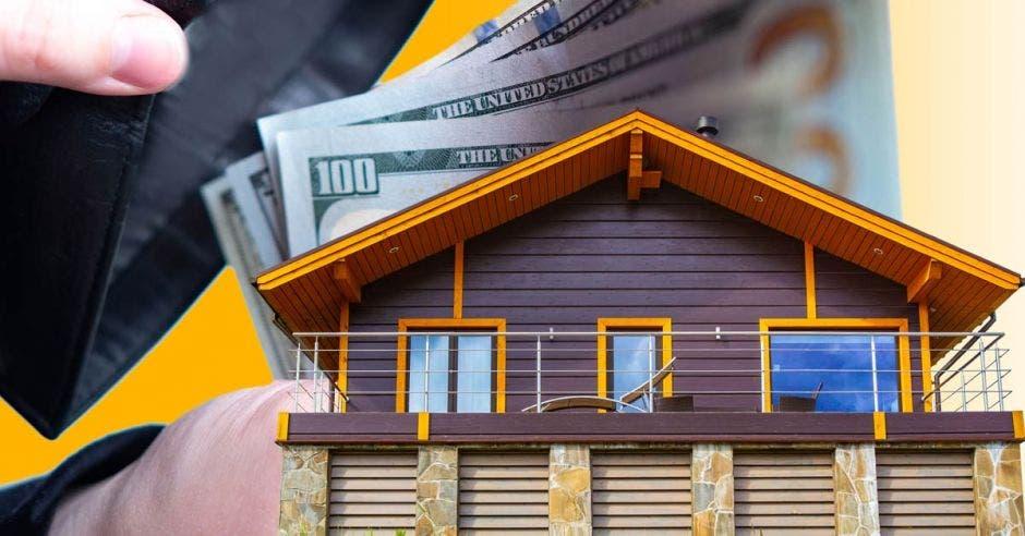 Casa en maqueta y persona tirando billetes encima