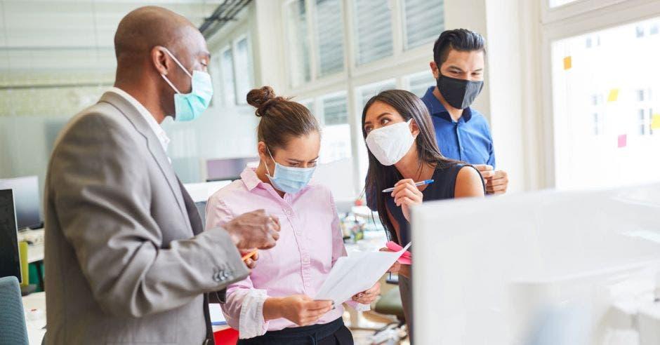 Un grupo de trabajadores en la oficina con mascarilla