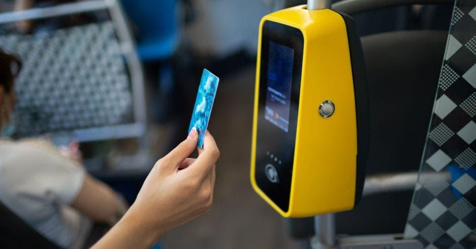 Persona pagando el tren con tarjeta de débito