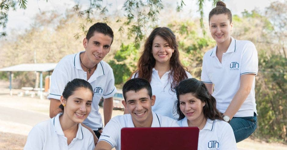 estudiantes en grupo frente a una computadora al aire libre