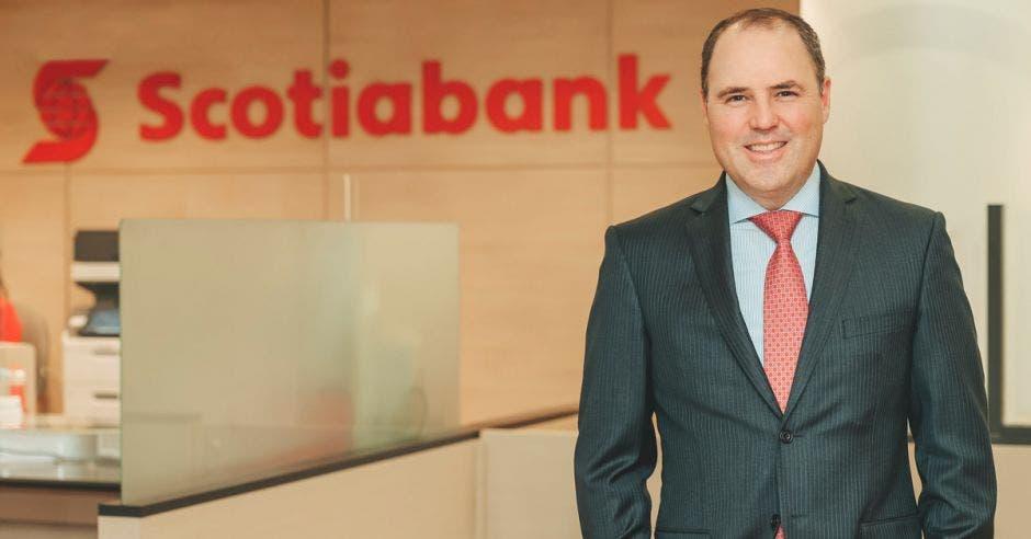 Hombre de traje frente a logo de Scotiabank