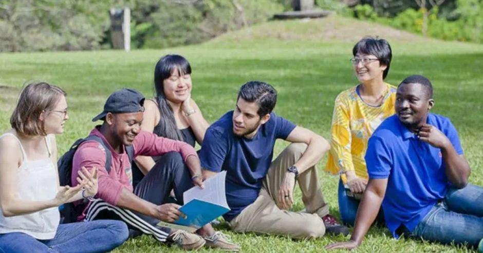 grupo de estudiantes sentados en el zacate con cuadernos y bultos