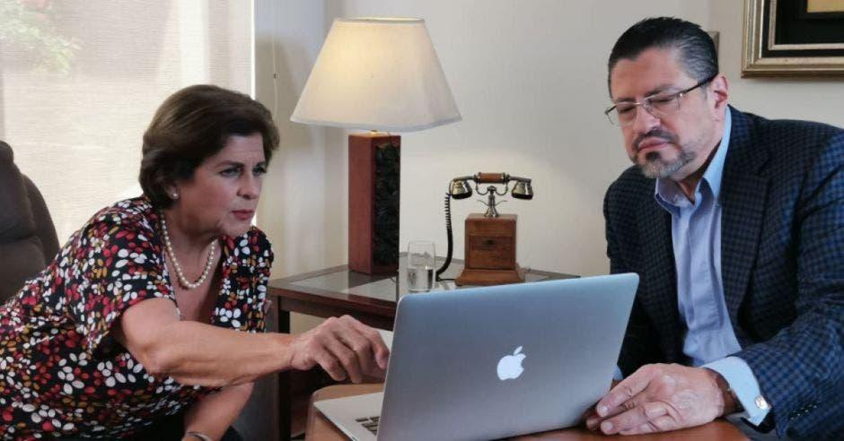 Pilar Cisneros y Rodrigo Chaves viendo laptop
