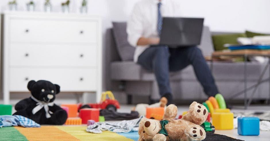 padre de familia trabajando desde la sala con juguetes en el piso