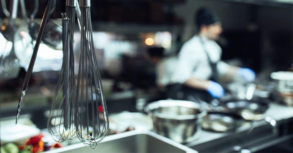 Utensilios de cocina en primer plano con chef de fondo