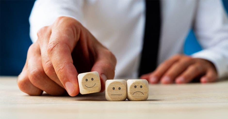 Mano sobre cubos con cara triste, alegre y media