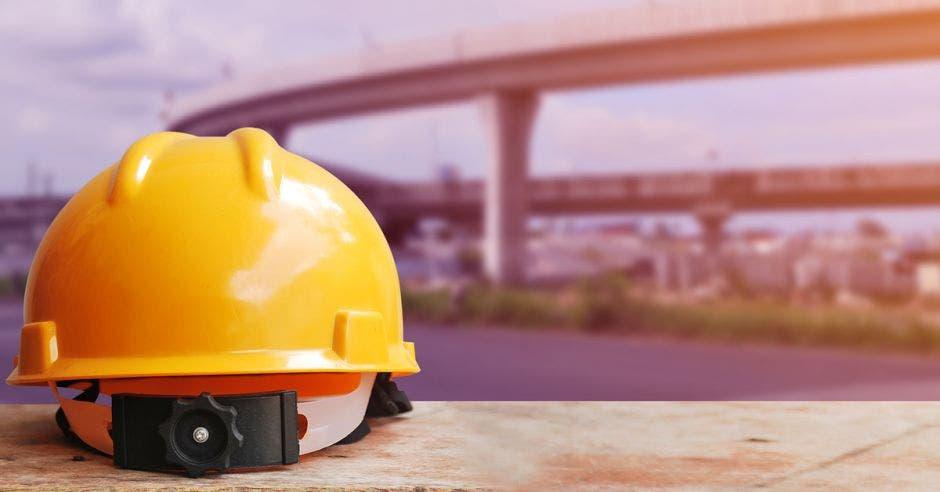 Un casco sobre una acera con una carretera elevada de fondo