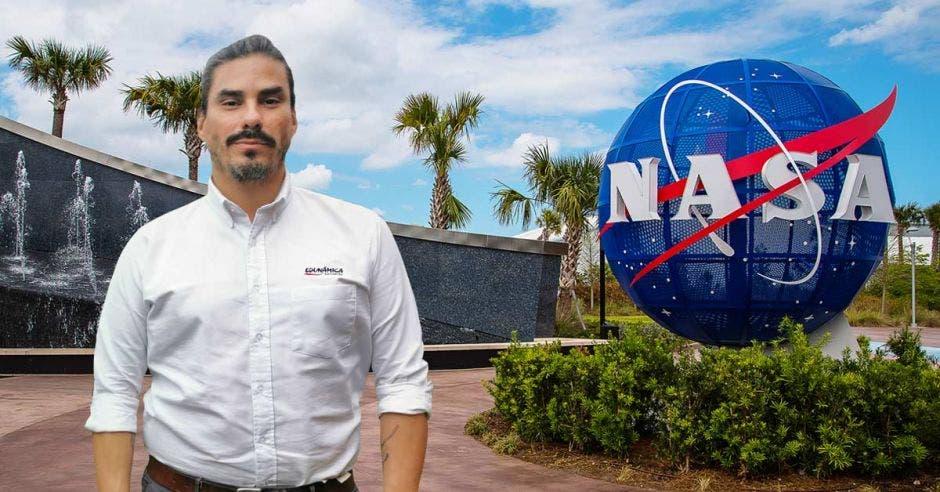 hombre de cabello cano con camisa blanca, de fondo instalaciones de la NASA