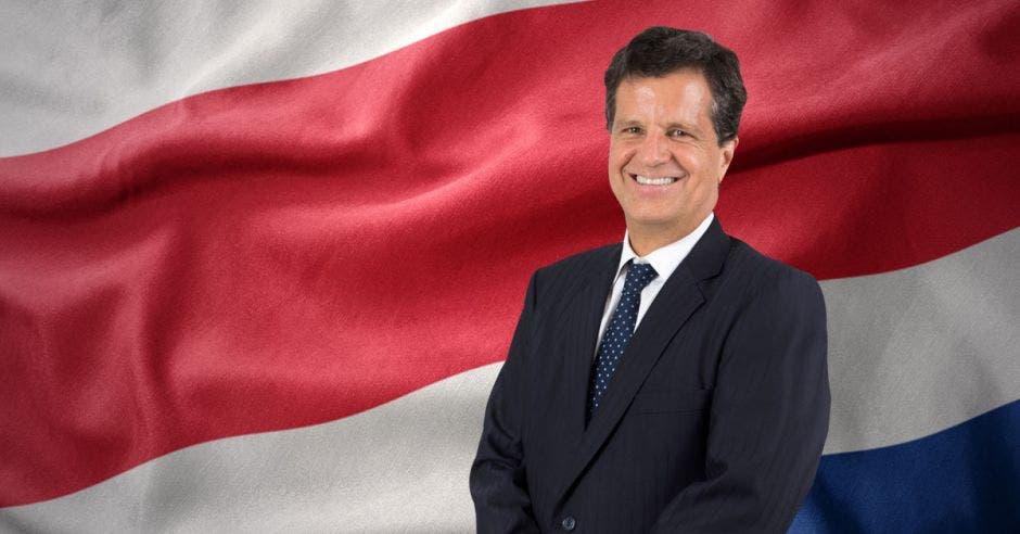 Hombre de traje frente a bandera de Costa Rica