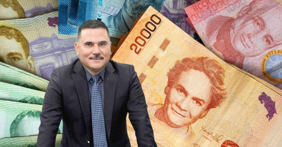 Hombre de traje frente a billetes ticos