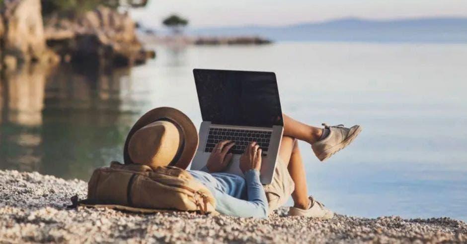 joven acostado en la arena frente al agua con su computadora