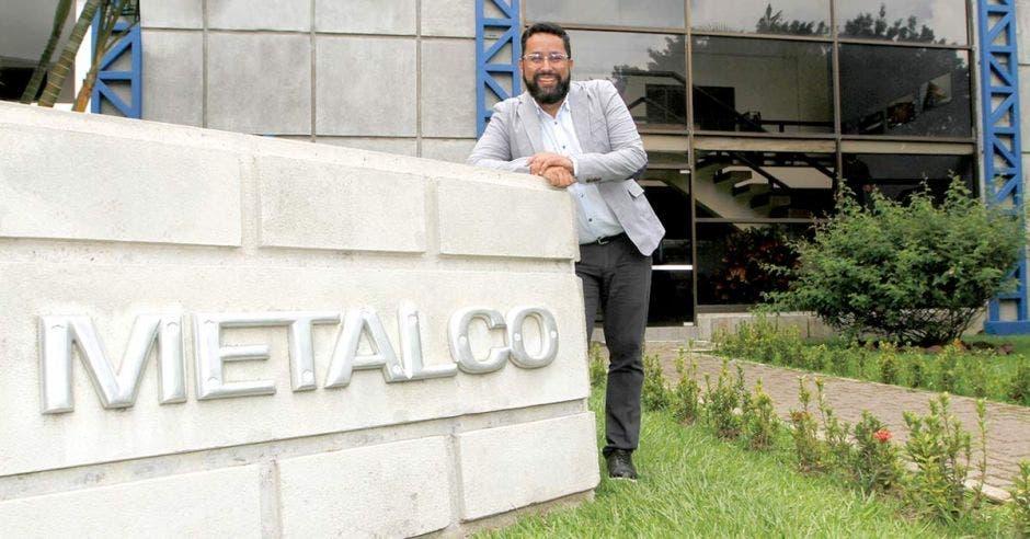 Jorge Luis Vega, gerente de Productos Planos de Metalco, detrás del rótulo con el nombre de la empresa, a la entrada de las instalaciones
