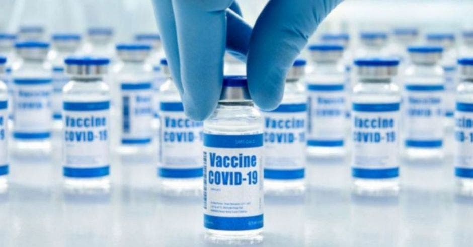 médico con guante mostrando una dosis contra la Covid-19