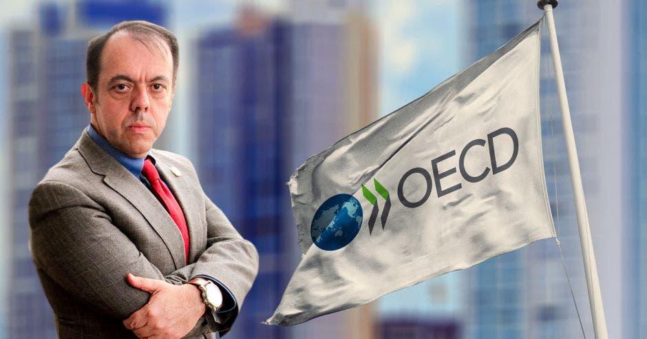 Hombre de traje y brazos cruzados ante bandera de la OCDE