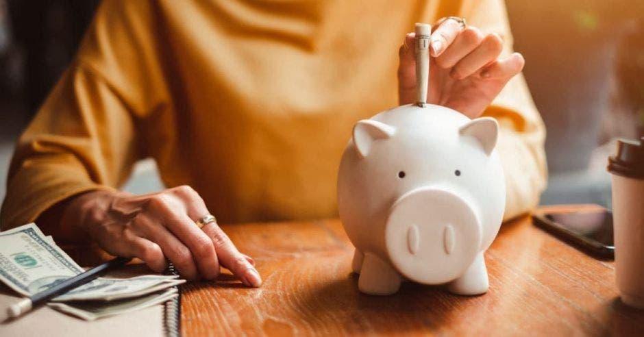 Mujer metiendo dinero en alcancía