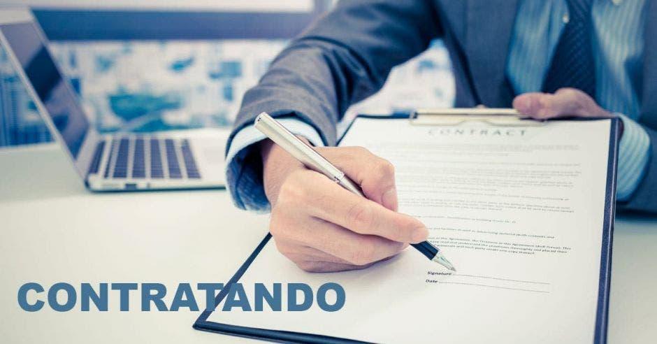 Mano de persona señalando contrato donde firmar
