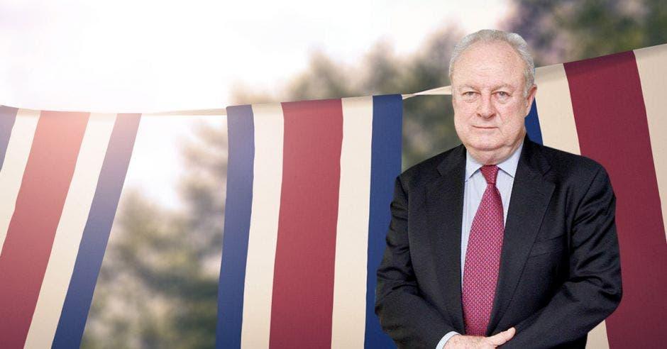 Hombre de traje frente a banderas