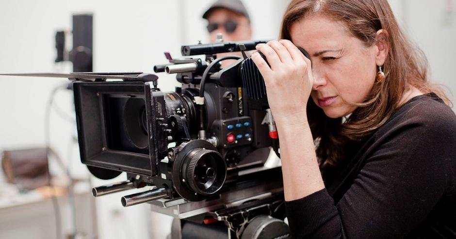 mujer detrás de cámara de filmación