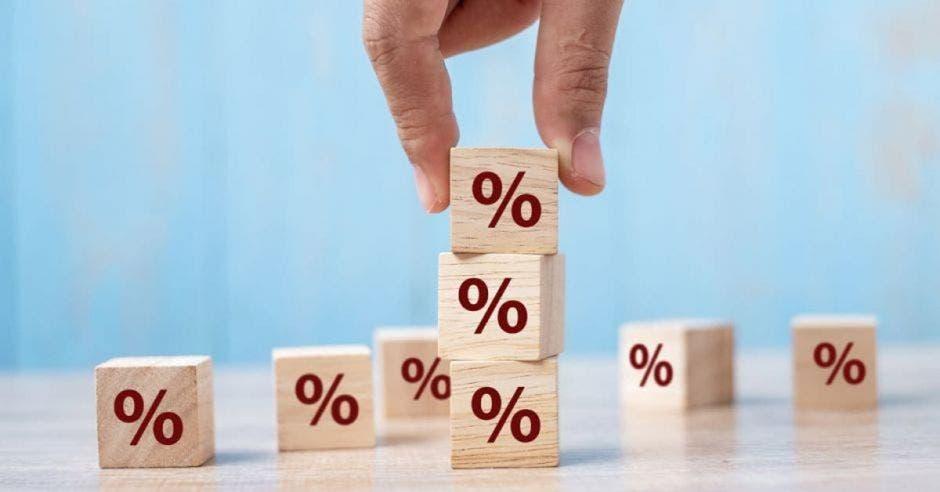 Mano de persona sostiene cubo con porcentaje