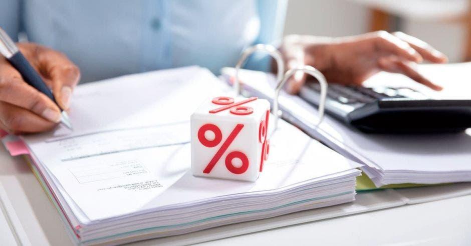 Cubo con porcentajes y persona haciendo cuentas en portafolio