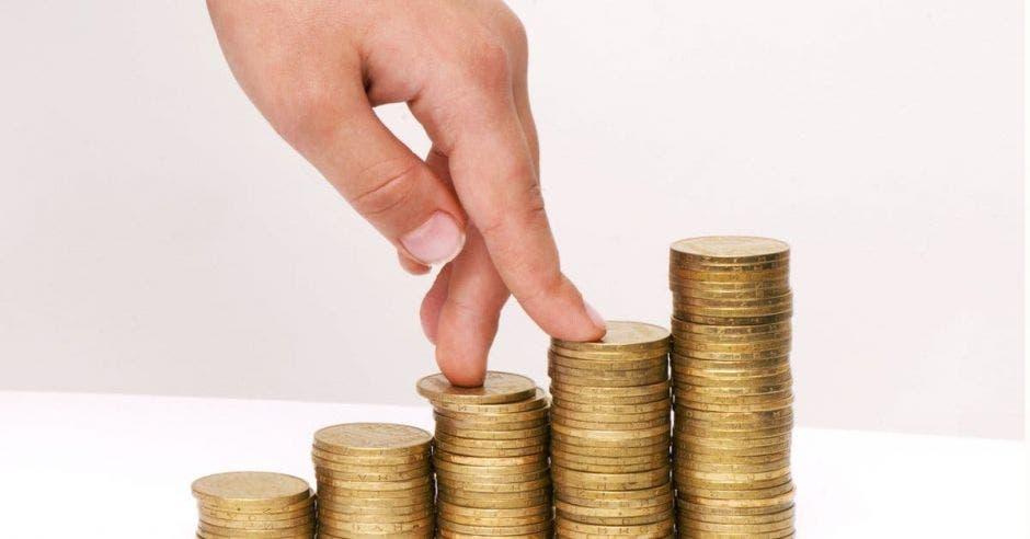 Monedas en columnas crecientes y mano subiendo