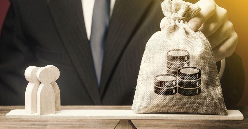 Balanza de bolsa de dinero y figuras que representan a personas