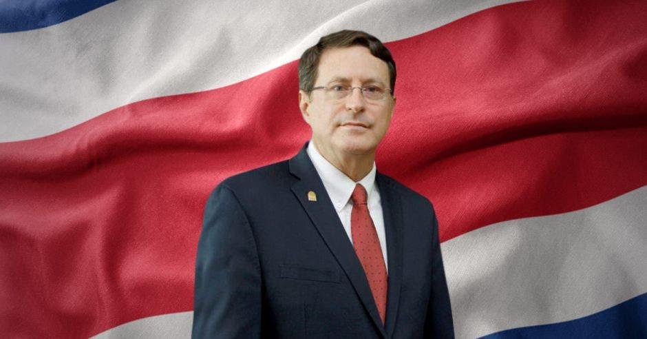 Román Macaya con una bandera de Costa Rica al fondo