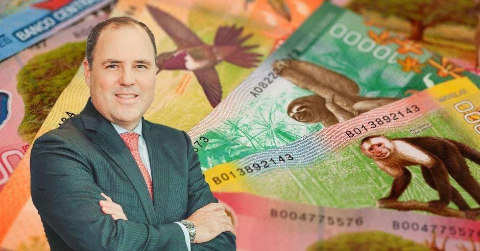 Hombre de traje y brazos cruzados frente a billetes de Costa Rica