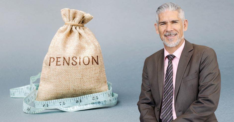 señor de cabello cano y barba, con traje café y camisa rosada, junto a costal con la palabra Pensión