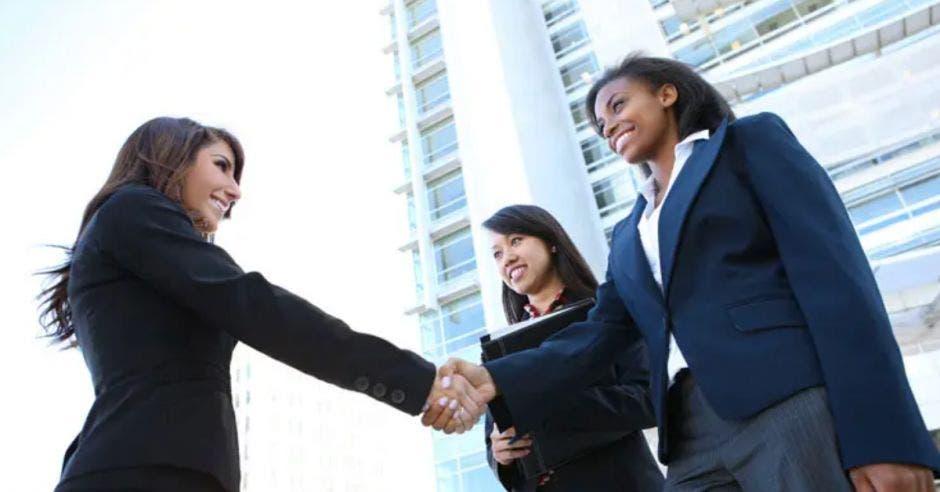 dos mujeres estrechando su mano en señal de trato