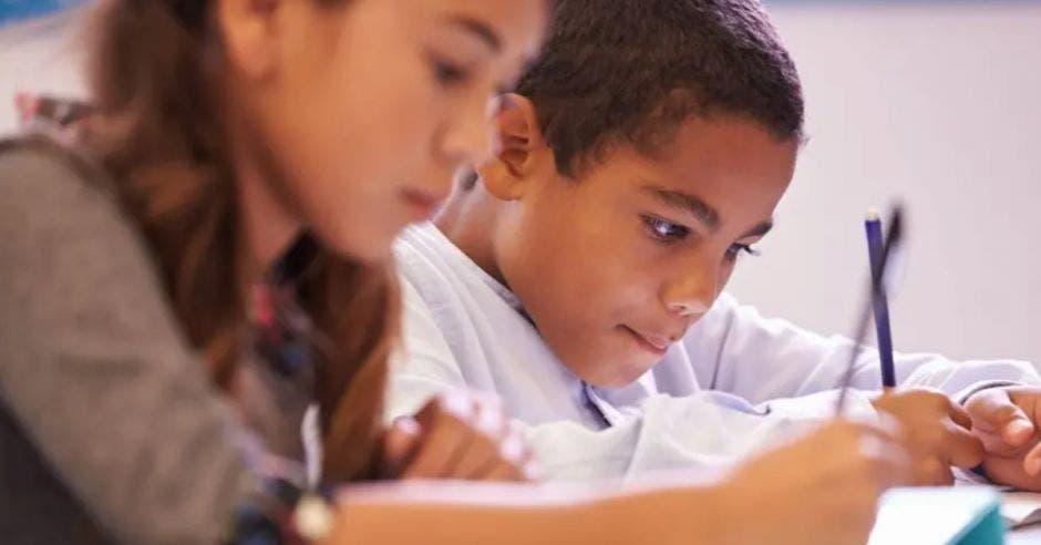 una niña y un niño escribiendo en sus cuadernos