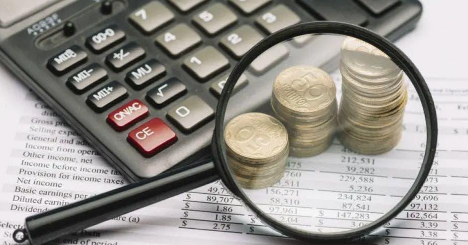 calculadora, monedas y una lupa