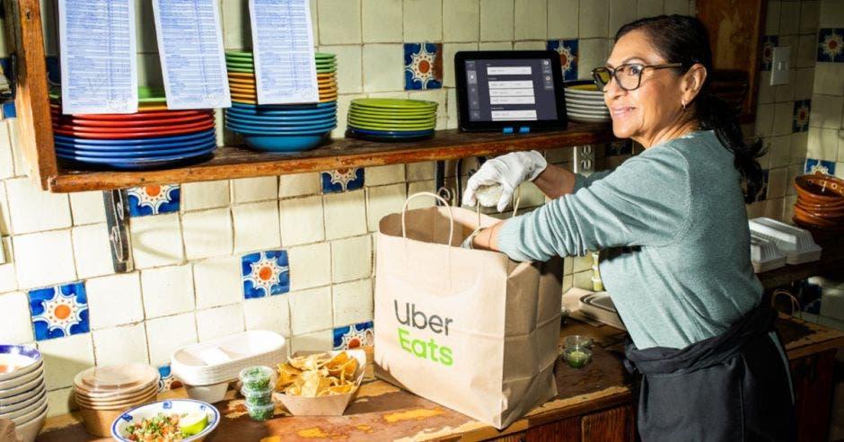 Mujer con paquetes de Uber Eats