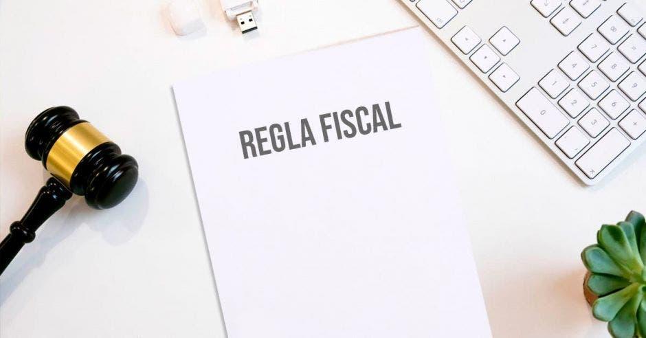 Mazo de juez y papel que dice regla fiscal