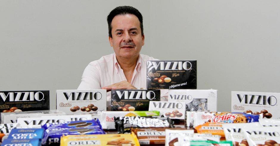 Walter Vega, Director Comercial de Ciamesa, detrás de una mesa llena de chocolates y galletas de las marcas Carozzi