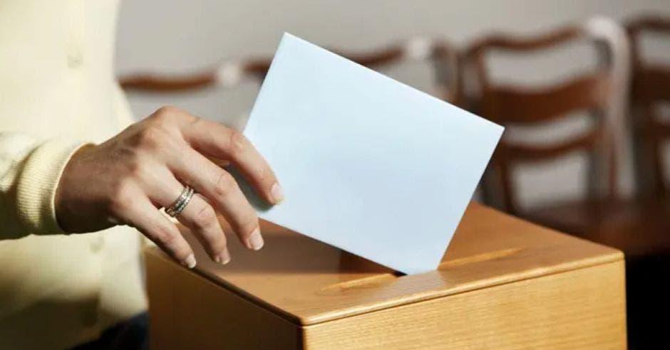 mano de mujer depositando una papeleta en un buzón