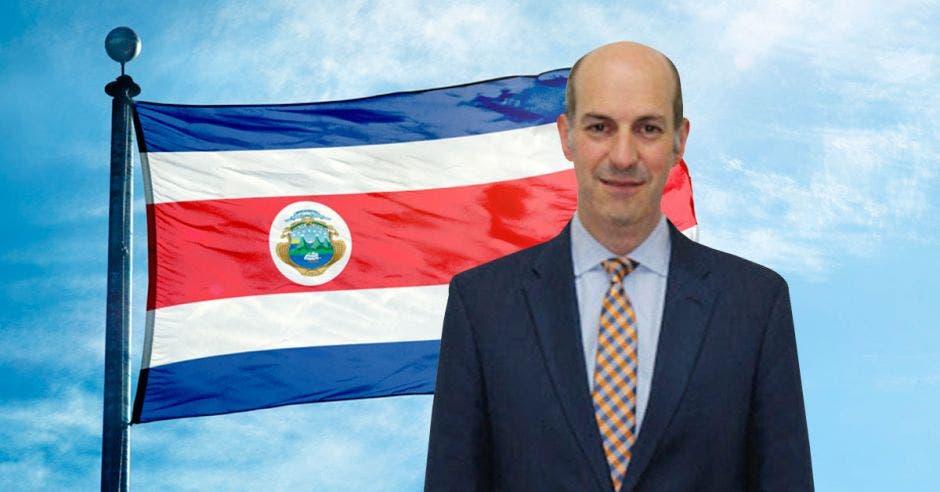 Hombre de traje y corbata frente a bandera de Costa Rica