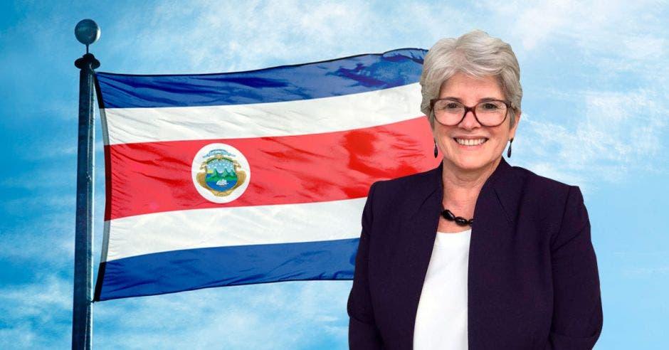 Mujer de traje frente a bandera
