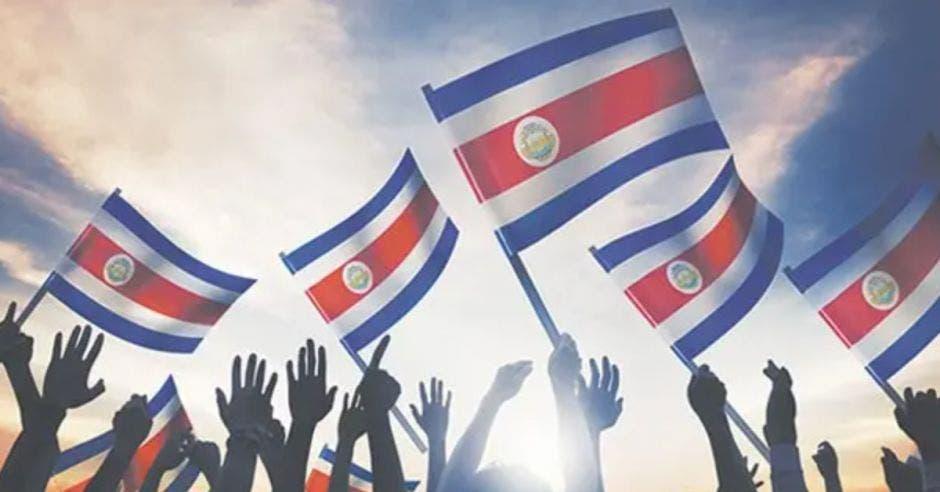 manos sosteniendo banderas de Costa Rica
