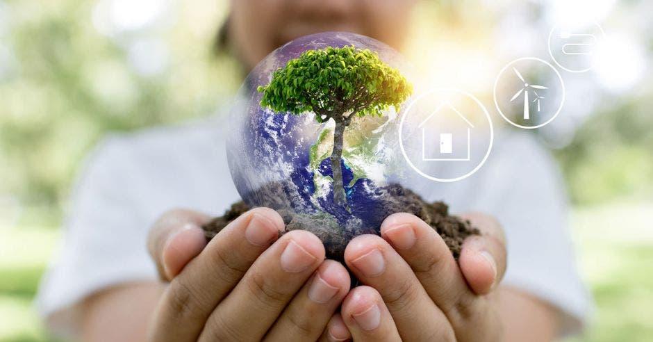 Persona sostiene en mano planeta en miniatura