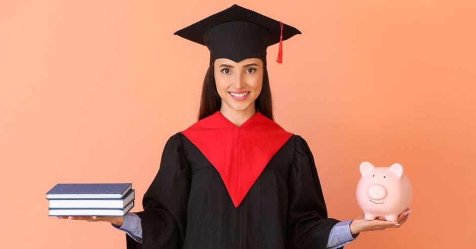 joven estudiante con toga y birrete, sosteniendo libros y alcancía de cerdito