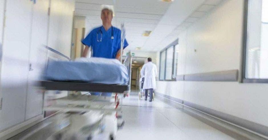 Un enfermero con una camilla en un pasillo de un hospital