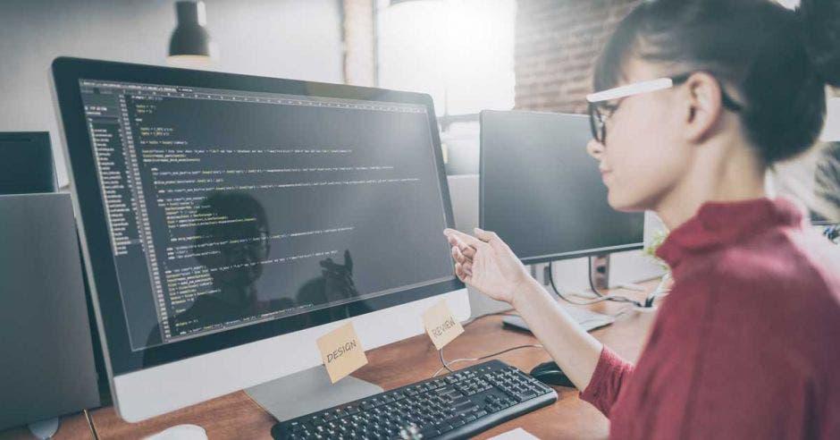 Mujer frente a computadora programando